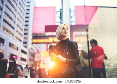 Mindful attractive blonde with trendy short haircut waiting for guide to looked at Hong Kong city planning sightseeing tour in morning drinking coffee to keep warm standing outdoors using free wifi