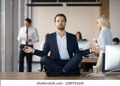 Mindful calm businessman in suit meditating at office sitting in lotus position on work desk, successful ceo executive doing yoga exercise at workplace, peace of mind, no stress free relief concept