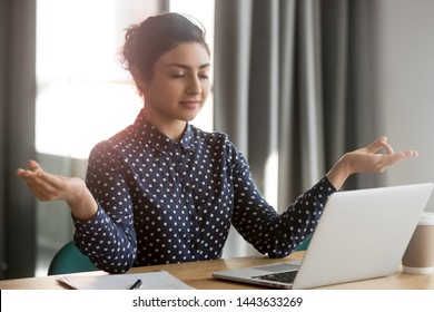 Mindful calm indian young business woman meditate at work desk with eyes closed, healthy hindu girl take break relax in office doing yoga at workplace feel balance no stress and peace of mind concept
