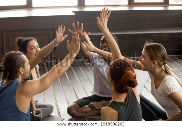 Mindful happy sporty diverse people join hands together at group seminar sitting on mats in studio, excited fit friends give high five supporting healthy lifestyle and unity in fitness goals concept