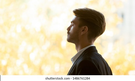 Mindful healthy business man calm face wear suit relax take deep breath of fresh air with eyes closed stand at window do yoga exercise feel peace of mind no stress free concept, close up side view