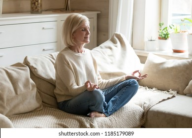 Mindful healthy mature woman practicing meditation at home, calm senior middle aged lady sitting on couch in lotus pose doing yoga for mental balance breathing air relaxing on stress free weekend