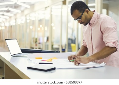 Mindful male architect in eyewear making sketching improving graphic correcting mistakes using laptop computer with mock up screen connected to fast 5G wireless during hard working day in office