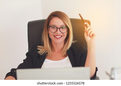 Mindful successful worker female sits in the office at the table and holds a pen in her hand.Happy face.Succesfull woman.Business woman