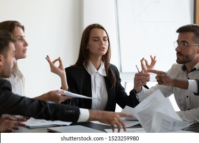 Mindful young business woman meditating, managing stress, ignoring annoyed arguing colleagues at workplace. Peaceful young female manager calming down during stressful working day at company office.