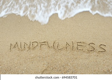 Mindfulness concept. The word Mindfulness written on sand.