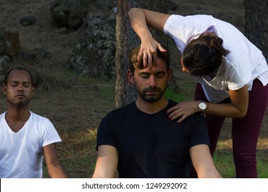 Mindfulness female teacher applying technique on young hipster forehead in forest park. Yoga meditation class with multi ethnic group of students in the woods. Relaxation exercise concept