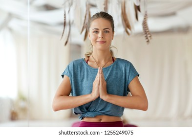 mindfulness, spirituality and healthy lifestyle concept - woman with namaste gesture meditating at yoga studio