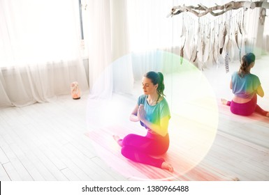 mindfulness, spirituality and healthy lifestyle concept - woman meditating at yoga studio over rainbow aura