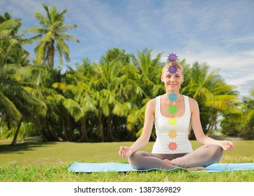 mindfulness, spirituality and outdoor yoga - couple meditating in lotus pose with seven chakra symbols over french polynesian park background