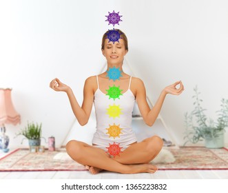 mindfulness, spirituality and relaxation concept - happy woman in underwear meditating in lotus pose at yoga studio with seven chakra symbols