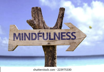 Mindfulness wooden sign with a beach on background