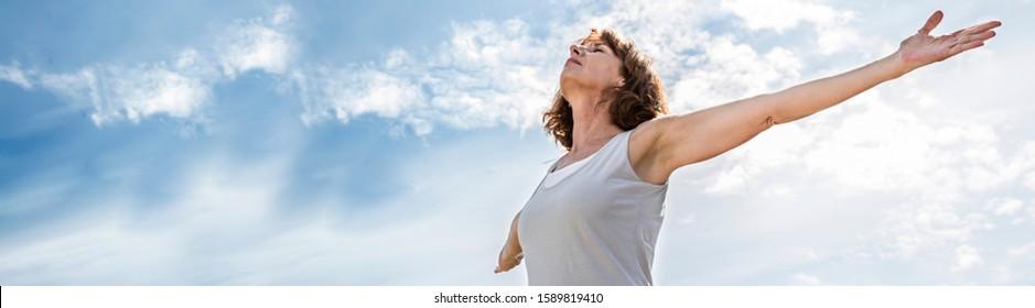 Achtsamkeit - Zen-Yoga-Dame öffnet ihr Chakra mit aufgewaufenen Armen, praktiziert Meditation für Freiheit über den sommerblauen Himmel, Low-Weitwinkel-Blick, langer Banner