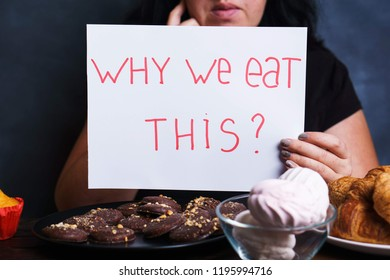 Mindless snacking, conscious nutrition, overeating, sugar addiction, stress, compulsive eating. Pensive woman sitting at table with lots of sweets holding plate  with Inscription Why we eat this