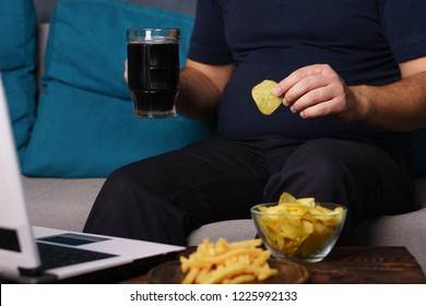 mindless snacking, overeating, lack of physical activity, laziness, homebody. fat overweight man engrossed in watching series at laptop eating fast food