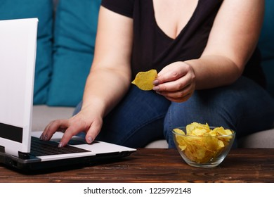 mindless snacking, overeating, lack of physical activity, laziness, homebody. fat overweight woman engrossed in watching series at laptop eating fast food