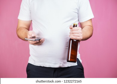 mindless snacking, weight gain, lack of physical activity, laziness, homebody. fat overweight man engrossed in surfing social media at smartphone drinking beer