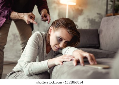 Mindlessly attacking. Beaten desperate woman reaching out smartphone and helpful phone while drunk alcoholic threating her