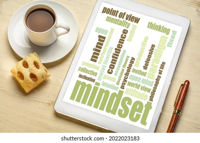 mindset  word cloud on a digital tablet with a cup of coffee and cookie
