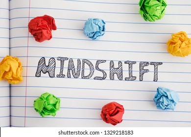 Mindshift. Word Mindshift on notebook sheet with some colorful crumpled paper balls around it. Close up.