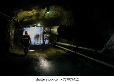 Mine worker walking down an underground mining tunnel