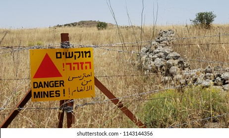 Minefield danger mines yellow warning sign on a barbed wire fence in the Golan Heights, Israel on the border with Syria and areas occupied by ISIS as of July 2018