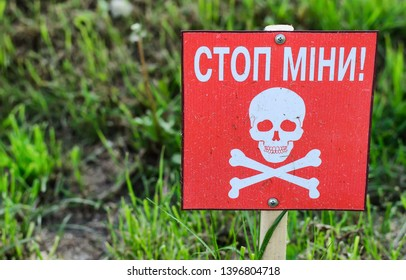 """Minefield warning sign (plate) with white skull and bones on red background and inscription in Ukrainian language """"Danger mines!"""", blurred background"""