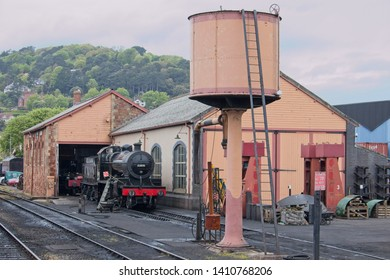 Minehead, Somerset, UK.  11th May, 2018. A view of Minehead West Somerset Railway engine shed with steam engine and a water tower in the foreground.