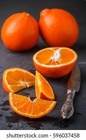 Mineola. Juicy sweet orange citrus fruit whole and sliced on a black background. Selective focus