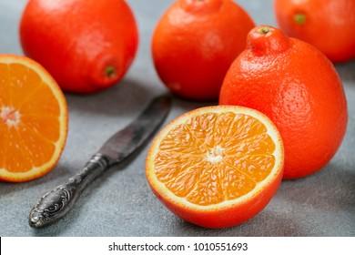 Mineola. Tangerine. Juicy sweet orange citrus fruit whole and sliced on a concrete background. Selective focus