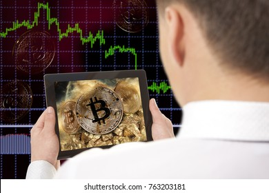 Miner. Businessman working on digital tablet. Gold bitcoin coin