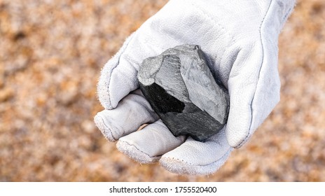 miner hand holding iron stone, metallic iron pyrite, steel, used in heavy industrial production. Mineral extraction concept.