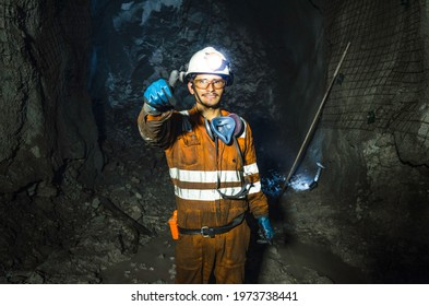 Miner in the mine. Well-uniformed miner inside mine raising thumb, conceptual photo