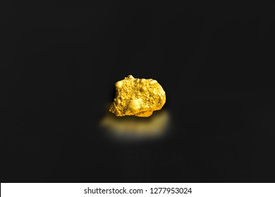 Miner of raw gold nugget or gold ore on black background, advertisement precious stone or lump of golden stone, business and financial concept idea. closeup Gold Miner industry concept.