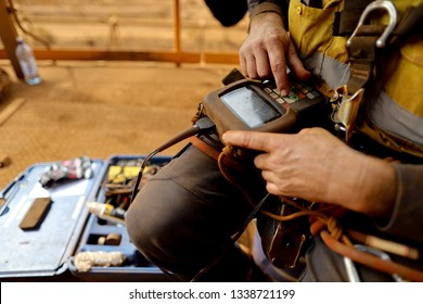 Miner rope access abseiler inspector  setting performing inspecting calibrating turning power on UT set Non-Destructive Testing (NDT) services prior to use construction mine site Perth, Australia