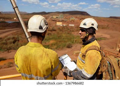 Miner senior business man supervisor wearing white safety hard hat protection holding folder paper work and conducting safety checking list on younger newest miner construction mine site Sydney