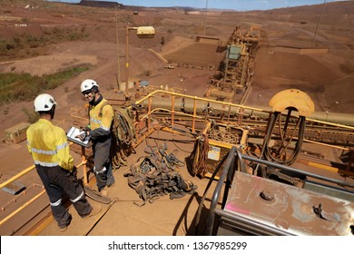 Miner senior businessman supervisor auditor wearing safety hard hat protection holding JHA folder paperwork conducting safety audits checking list younger newest miner construction site Sydney