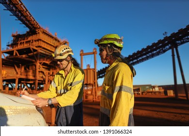 Miner supervisor engineer wearing safety fall protection helmet read and sign permit to work before hand over working at height paper book to contractor construction mine site, Sydney, Australia
