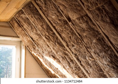 Mineral glass wool and styrofoam in a wooden frame on a inclined wall near the wooden ceiling and a window in a private house. Warming the walls with fiberglass and foam plastic.
