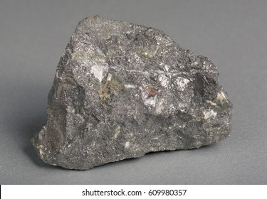 Mineral stone magnetite (lodestone) on gray background.  Magnetite is the most magnetic of all minerals on Earth .