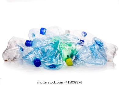 Mineral water and fizzy drinks bottles crushed and crumpled against white isolated background