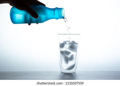 Mineral water with a piece of ice in the double glass close up on white background.