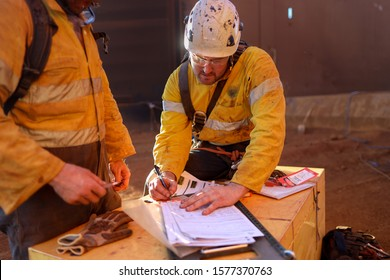 Miners wearing a white fall protection safety helmet signing name, signature in from safety control permit to work isolation lock box prior to work on opening field construction mine site Australia