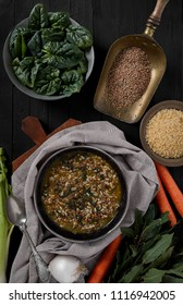 Minestrone with fresh spinach, rice and brown lentils, on black wooden background, top view shot.