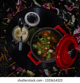 Minestrone, italian vegetable soup with ingredient on a black table. Top view. Homemade delicious minestrone soup with basil. A red bowl of minestrone soup with crackers