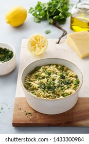 Minestrone, Italian vegetable soup with pasta and savoy cabbage. Served with cilantro pesto and parmesan. Healthy vegetarian food.