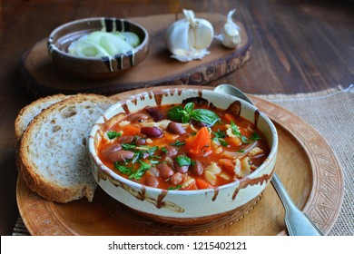 Minestrone soup with beans and vegetables in stoneware bowl with bread in a rustic setup
