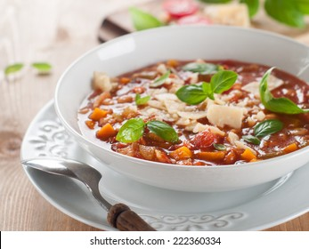 Minestrone soup with cheese and basil, selective focus