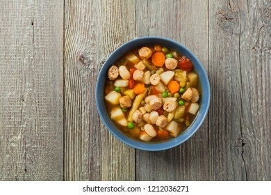 Minestrone soup with crostini. Natural wooden background. Top view.