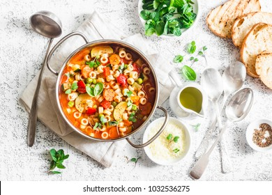 Minestrone soup in a pan on a light table, top view. Italian soup with pasta and seasonal vegetables. Delicious vegetarian food concept. Flat lay